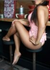 sweet escort girl is sitting at the bar counter