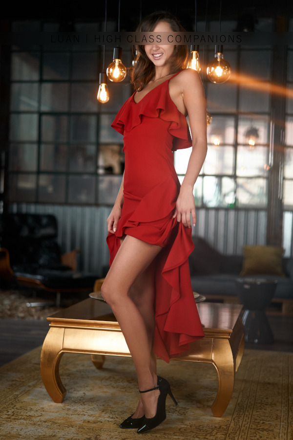 Elite Companion in a red dress